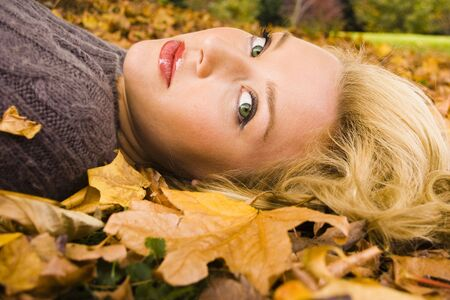 Young girl lying in the Autumn fall leaves photo