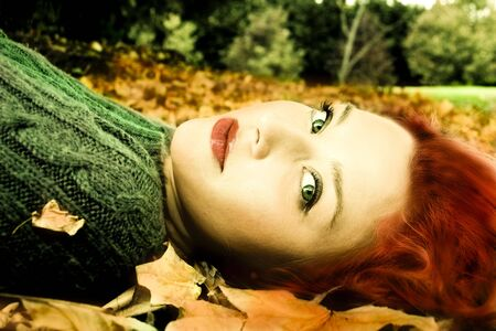 lying in leaves: Young girl lying in the Autumn fall leaves Stock Photo