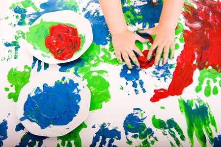 Little hands painting with red green blue Stock Photo
