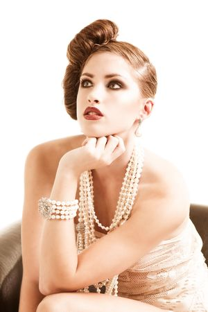 An attractive young woman sitting in a brown leather chair. She is wearing white lace lingerie with pearls. Vertical shot.