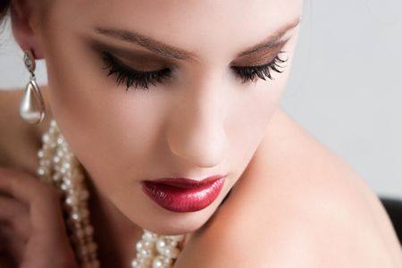 Attractive young woman wearing a pearl necklace and earrings. Horizontal shot. Stock Photo