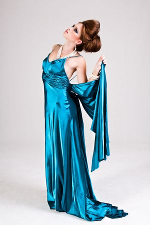 An attractive young woman standing in a blue satin dress and looking up. Vertical shot. photo