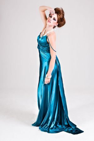 Attractive young woman standing in a blue satin dress, wearing pearls and touching her head. Vertical shot. photo