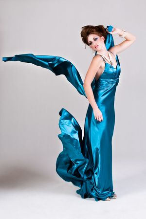 Attractive young woman standing in a blue satin dress as it blows in the wind. Vertical shot. photo