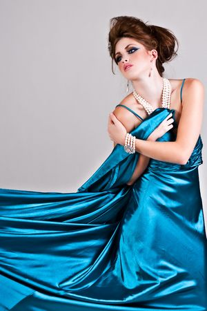 Attractive young woman standing in a blue satin dress that is being pulled to the side. Vertical shot. photo