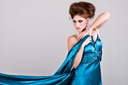 Attractive young woman standing in a blue satin dress that is being blown in the wind. Horizontal shot. photo