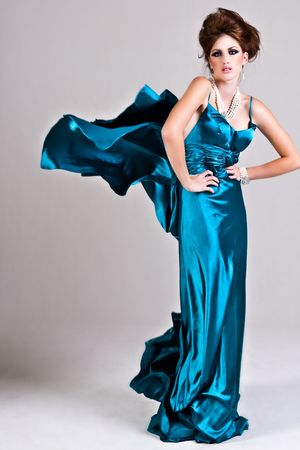Attractive young woman standing with her hands on her hips in a blue satin, wind blown dress. Vertical shot. Stock Photo - 6505588