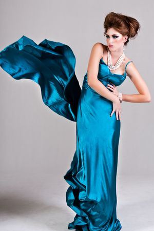 Attractive young woman standing with her hands on her hips in a blue satin, wind blown dress. Vertical shot. photo