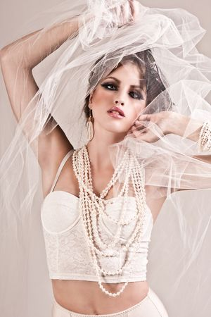 Attractive young woman wearing a veil, a pearl necklace and a bracelet. Vertical shot. Stock Photo - 6505579