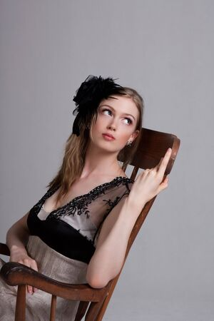 Attractive young woman wearing a black feather hairdressing and sitting in a rocking chair. Vertical shot. photo