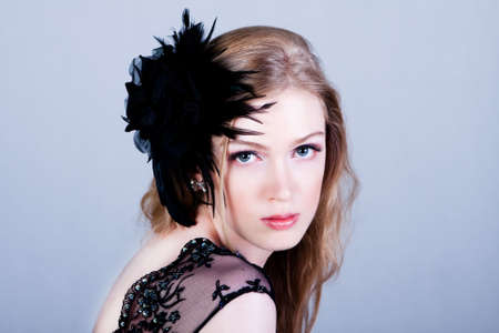 Attractive young woman wearing a black lace top and a black feather hairdressing. She is looking over her shoulder. Horizontal shot. photo