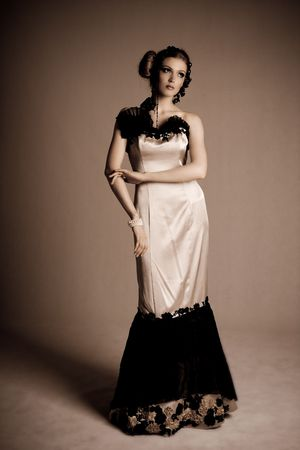 evening gown: Attractive young woman wearing an evening gown of black lace and white satin. Vertical shot. Stock Photo