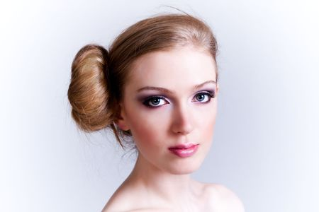 Attractive young woman with her hair in a bun looks towards the camera. Horizontal shot. photo