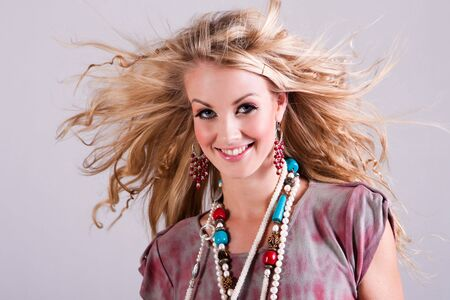 Attractive young woman with wind-blown hair smiles towards the camera. She is wearing a tie-dyed shirt and beaded necklaces. Horizontal shot. Isolated on grey. photo