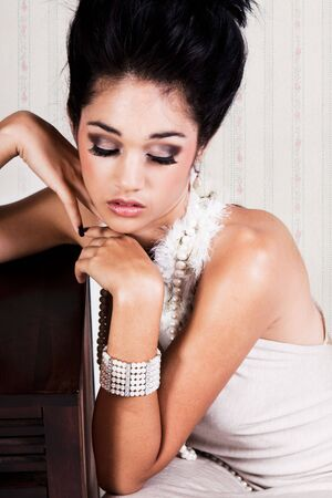 Attractive young woman in a glamorous dress and accessories leans against wood furniture with her eyes closed. Vertical shot. photo