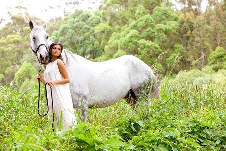 An attractive young woman in a white, flowing dress holds the reins of a white horse. She is standing in an idyllic meadow. Horizontal shot. Stock Photo