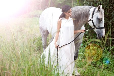 An attractive young woman in a white, flowing dress guides a white horse through an idyllic meadow. There is a lighting effect in the upper left corner of the image. Horizontal shot.