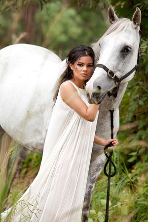 An attractive young woman in a white, flowing dress holds the reins of a white horse. She is standing in a wooded area. Vertical shot. Stock Photo
