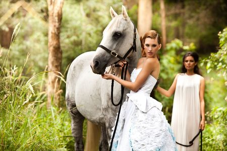 Two young women in flowing white dresses stand next to a white horse in a serene, wooded area. Horizontal shot.