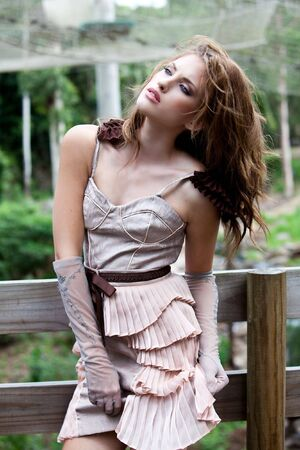 An attractive young woman poses against an outdoor wooden fence. She is wearing stylized clothing. Vertical shot.