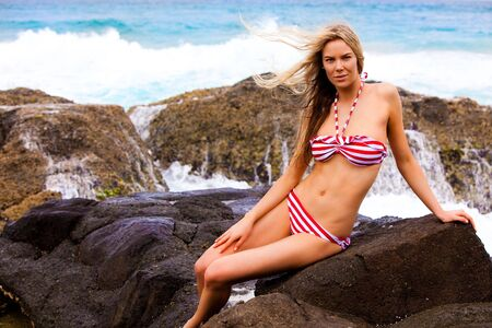 An attractive young woman wearing a striped bikini is sitting on rocks at the beach with surf in the background.  She is looking at the camera with a serious expression.  Horizontal shot. photo