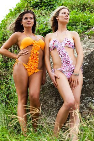 Low angle portrait of two attractive young women wearing bikinis and standing in the grass on a hillside next to a rock. Vertical shot. photo