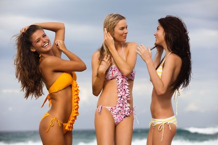 Three attractive young women standing at the beach and wearing swimsuits, with the surf visible in the background. All three are smiling, with two of the women looking at each other and the third looking at the camera. Horizontal shot. Stock Photo - 6635694