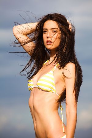 Portrait of an attractive young woman wearing a bikini and posing against a cloudy sky.  She has one hand on the back of her  head and is staring off camera with a blank expression. Vertical shot. photo