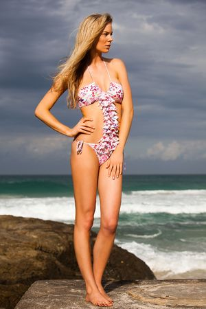 Full length view of an attractive young woman posing in a bikini on rocks on a cloudy beach.  She has one hand on her hip and is staring off into the distance. Vertical shot. photo