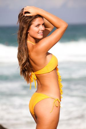 Portrait of an attractive young woman at the beach.  She is wearing a bikini and holding her hair out of her face with both hands. The surf can be seen out of focus in the background. Vertical shot.