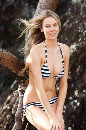 Portrait of an attractive young woman wearing a striped bikini and leaning on driftwood next to a large rock formation. She is smiling slightly at the camera. Vertical shot. Stock Photo - 6635651