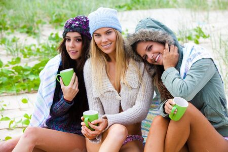 Portrait of three attractive young women smiling and sitting together on a beach.  They are bundled up against the chilly weather and are holding green coffee cups. Horizontal shot. Stock Photo - 6635684