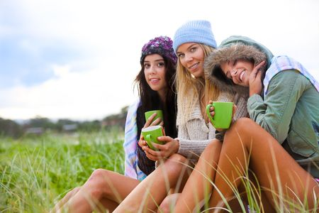 amis caf�: Portrait of three attractive young women smiling and sitting together in the grass at the coast.  They are bundled up against the chilly weather and are holding green coffee cups. Horizontal shot.
