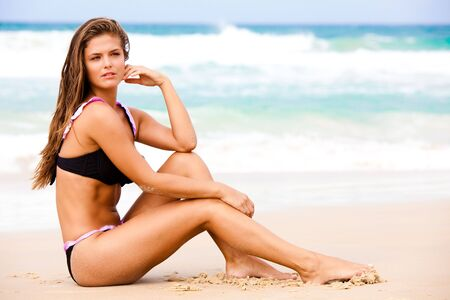 An attractive young woman wearing a black bikini sits on a beach with her elbow on her knee and her hand to her head.  Surf can be seen in the background. Horizontal shot. photo