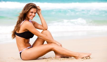 An attractive young woman wearing a black bikini sits on a beach with her elbow on her knee and her hand to her head.  Surf can be seen in the background. Horizontal shot. Stock Photo