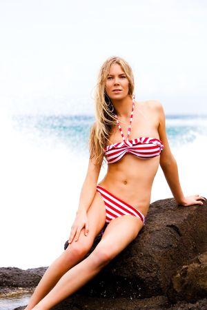 An attractive young woman sits on rocks at the beach with her hand on her leg. She is wearing a red and white striped bikini. Vertical shot. photo