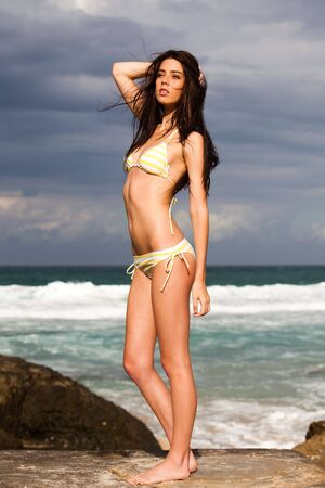 An attractive young woman wearing a bikini is standing on rocks at the beach with surf in the background. Vertical shot. photo