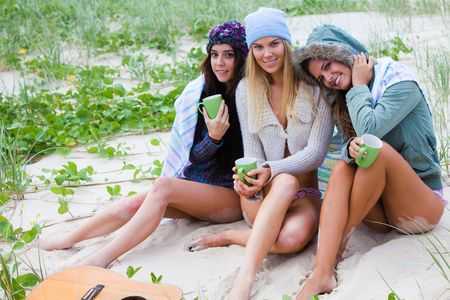 Three attractive young women in swimsuits huddle together on the beach. They are wearing upper body clothing for warmth. Horizontal shot. photo