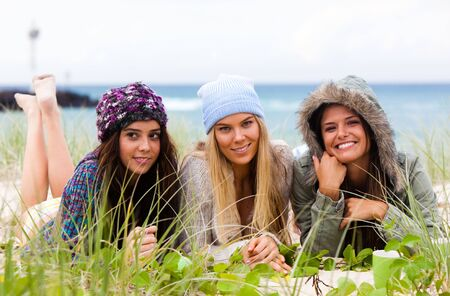 Three attractive young women lie on the beach together with the ocean in the background. Horizontal shot. photo