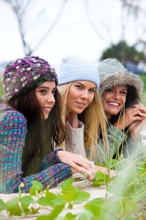 Three attractive young women lie on the beach together. They are all wearing hats to keep warm. Vertical shot. photo