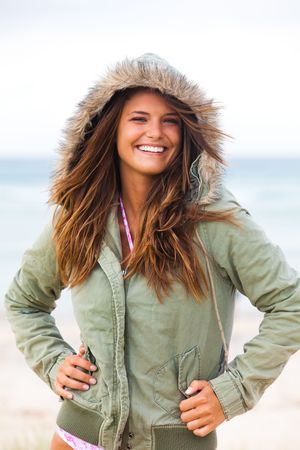 An attractive young woman is wearing a coat at the beach and standing with her hands on her hips. Vertical shot.