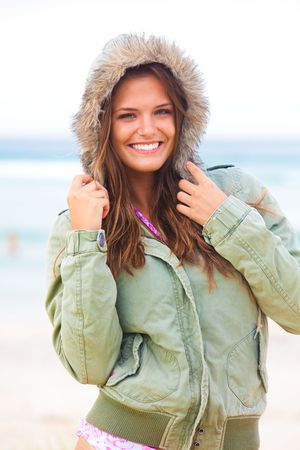An attractive young woman is wearing a coat at the beach and standing with her hands on the hood. Vertical shot. photo