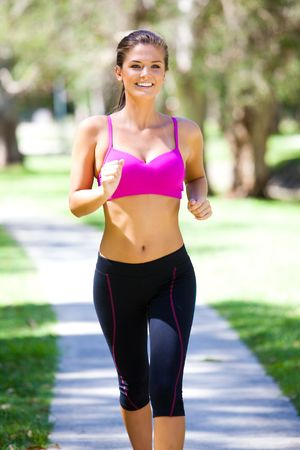 activewear: Portrait of a young woman jogging in an outdoor setting. Vertical shot.