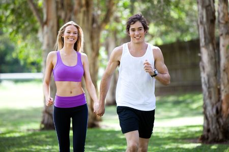 Portrait of a smiling young couple exercising in an outdoor setting while holding hands. The man is jogging, and the woman is walking. Horizontal shot. Stock Photo