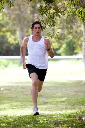 man only: Full length view of a young man jogging in an outdoor setting. He is wearing a tank top and shorts. Vertical shot. Stock Photo