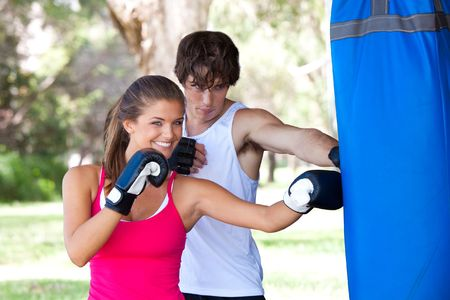 woman boxing gloves: A young couple boxing for fitness. The man is looking at the boxing bag, and the woman is looking at the camera. Horizontal shot.