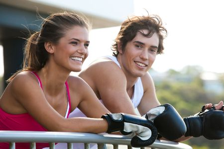 Young couple leaning over a railing in an outdoor setting. They are both wearing boxing gloves and smiling. Horizontal shot. photo