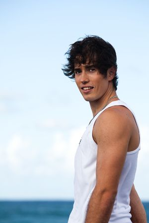 Portrait of a young man with a white tank top and wind-blown hair, looking over his shoulder at the camera. The ocean can be seen out of focus in the background. Vertical shot.
