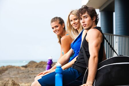 duffle: One young man and two young women sitting and relaxing by a building at the beach. The young man has a duffle bag, and two water bottles are visible. They are all dressed in tank tops and shorts and looking at the camera. Horizontal shot. Stock Photo