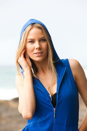 sleeveless hoodie: Portrait of a young woman wearing a sleeveless hoodie and headphones. She is at the beach and looking at the camera with a slight smile. Vertical shot.